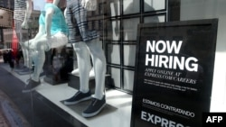 FILE - A now hiring sign is posted in the window of a clothing store on June 6, 2014 in San Francisco, California.