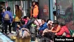5일 전남 순천시 북부시장의 한 버스정류장에서 유권자들이 버스를 기다리며 각 총선 후보들의 경쟁적인 유세장면을 지켜보고 있다.