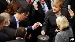 Thủ tướng Đức Angela Merkel (phải) bỏ một lá phiếu của mình tại Quốc hội Liên bang Đức ở Berlin, Đức, ngày 4/12/2015.