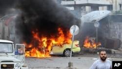 Trong bức ảnh được công bố bởi hãng tin chính thức của Syria SANA, những người Syria tụ tập phía trước một chiếc xe ô tô đang bốc cháy tại hiện trường vụ đánh bom tự sát ở Tartus, Syria, ngày 23 tháng 5 năm 2016.