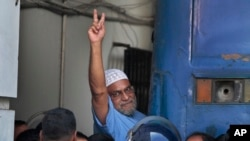 Mir Quasem Ali, a senior leader of the Bangladesh's largest Islamist party Jamaat-e-Islami shows victory sign as he enters a police van after a special tribunal sentenced him to death in Dhaka, Bangladesh, Nov. 2, 2014.