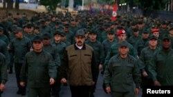 Venezuela's President Nicolas Maduro walks next to Venezuela's Defense Minister Vladimir Padrino Lopez and Remigio Ceballos, Strategic Operational Commander of the Bolivarian National Armed Forces, during a ceremony at a military base in Caracas, Venezuela.