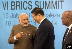 印度总理莫迪和中国国家主席习近平在巴西出席金砖五国会议领导人合影期间交谈。(2014年7月15日)