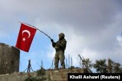 Seorang tentara Turki mengibarkan bendera di Gunung Barsaya, timur laut Afrin, Suriah, 28 Januari 2018. (Foto: REUTERS/Khalil Ashawi)