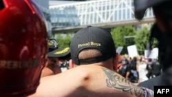 FILE - A person wears a hat of U.S. far-right men's organization Proud Boys during a campaign rally for Patriot Prayer founder and Republican Senate candidate Joey Gibson in Portland, Ore., Aug. 4, 2018.