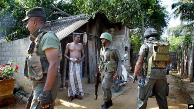 Seorang warga Tamil mengamati anggota tentara Sri Lanka yang sedang menggelar operasi pencarian di Jaffna pasca perang saudara di wilayah itu (Foto: dok). Partai utama suku Tamil mendesak PBB agar menebus kegagalan yang telah diakuinya dalam upaya melindungi warga sipil Tamil dengan memulai penyelidikan internasional (16/11).