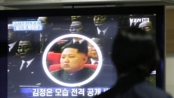 A worker in Paju, South Korea, looks at a picture of North Korea's Kim Jong Un on a TV news show. Experts say Kim Jong Il could be preparing his third and youngest son for leadership.