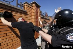 FILE - Interior Ministry members detain anti-gay protesters during the LGBT Equality March in Kyiv, Ukraine, June 6, 2015.