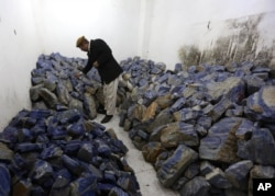FILE - An Afghan businessman checks lapis lazuli at his shop in Kabul, March 28, 2016. The brilliant blue stone, prized for millennia, is found almost exclusively in Afghanistan and is a key part of the nation's mineral wealth.