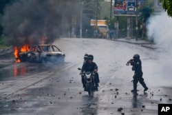 A police officer aims his shotgun at two men riding a motorcycle during a protest against Nicaragua's President Daniel Ortega in Managua, May 28, 2018.
