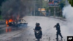 FILE - A police officer aims his shotgun at two men riding a motorcycle during a protest against Nicaragua's President Daniel Ortega in Managua, Nicaragua, May 28, 2018.