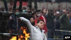 Người biểu tình ném đá vào cảnh sát trong khi lực lượng an ninh bắn hơi cay vào đoàn biểu tình khi cuộc biểu tình bước sang ngày thứ ba ở Quảng trường Tahrir, Ai Cập
