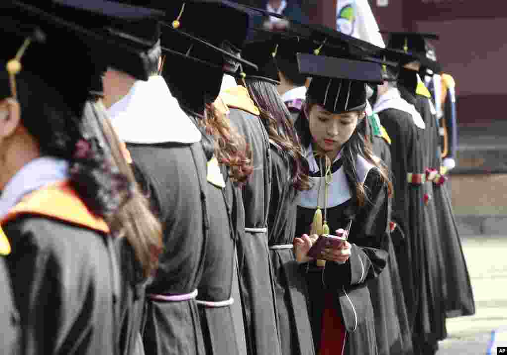 South Korean graduate Yoo Hye-jin checks her smartphone during a graduation ceremony at Sungkyunkwan University in Seoul.