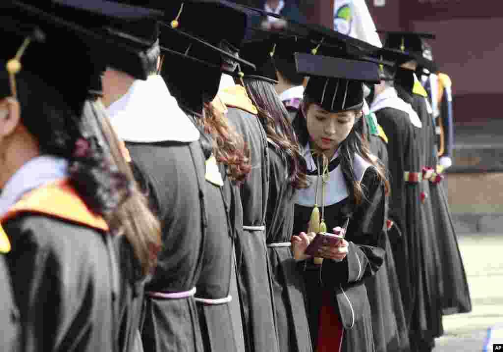 مراسم فارغالتحصيلی دانشگاه سانکوانکوان در سئول. دانشجوی فارغالتحصيل يو هوئیجين تلفن هوشمند خود را چک میکند.
