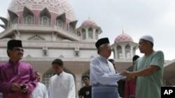 Malaysia's Prime Minister Najib Razak (2nd R) meets people after Friday prayers at the Putra Mosque in Putrajaya outside Kuala Lumpur, 10 Jul 2010