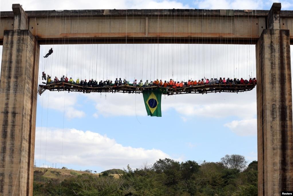 在巴西利梅拉市,90个人坐在桌子旁边吃烧烤,桌子使用高科技悬挂在一座桥下面(2017年7月30日)