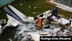 Petugas pemadam kebakaran memeriksa puing-puing pesawat penumpang kecil yang jatuh di Guatemala City 14 Mei 2009, sebagai ilustrasi. (Foto: REUTERS/Rodrigo Arias)