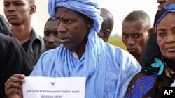 ປະຊາຊົນໃນນະຄອນຫຼວງ Bamako ຂອງມາລີ ຖືປ້າຍບອກຂ່າວ ກ່ຽວກັບບ່ອນບໍລິຈາກການຊ່ອຍເຫຼີອແກ່ ພວກປະຊາຄົມຕ່າງໆທີ່ ໄດ້ຮັບຜົນກະທົບຈາກຄວາມວຸ້ນວາຍໃນພາກເໜືອຂອງປະເທດ. ວັນທີ 10 ເມສາ 2012.