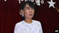 Burmese pro-democracy leader Aung San Suu Kyi talks to reporters at the headquarters of her National League for Democracy party, April 30, 2012, in Rangoon.