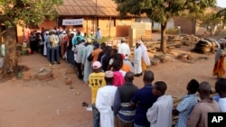 A photo taken April 13, 2014 shows people lining up at a poling station to cast their votes in Bissau, Guinea-Bissau.