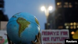 Seseorang memegang bola bumi selama gerakan Global Climate Strike of the Fridays for Future di Sao Paulo, Brazil, 20 September 2019. (Foto: REUTERS/Nacho Doce)