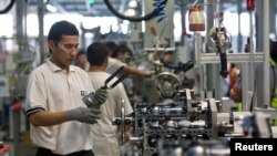 FILE - Employees work on an assembly line at the General Motors Powertrain-Uzbekistan plant in Tashkent, Aug. 31, 2012.