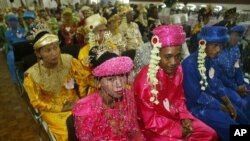 FILE - Indonesian couples wait for their turn to wed during a 47-couple mass wedding ceremony in Jakarta, Indonesia, in 2005.