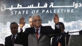 Palestinian President Mahmoud Abbas, waves to the crowd during celebrations for their successful bid to win U.N. statehood recognition in the West Bank city of Ramallah, December 2, 2012.