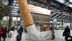 FILE - A symbolic cigarette butt is set up inside Gare de Lyon railway station, in Paris, Dec. 4, 2012, as part of a publicity campaign against rudeness, by Paris's public transport authority.