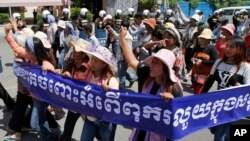 "Cambodian activists shout slogans during a march toward the National Assembly, in Phnom Penh, Cambodia, Thursday, May 29, 2014. Some 300 activists on Thursday delivered petitions to the National Assembly and Anti-Corruption Unit headquarters to demand the government to stop giving land concession to private companies. The banner reads "" Absolutely against the corruption in the society."" (AP Photo/Heng Sinith)"