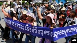Cambodian activists shout slogans during a march toward the National Assembly, in Phnom Penh, Cambodia, Thursday, May 29, 2014.