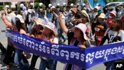 "In this file photo, Cambodian activists shout slogans during a march toward the National Assembly with the banner that reads ""Absolutely against the corruption in the society,"" in Phnom Penh, Cambodia, Thursday, May 29, 2014."
