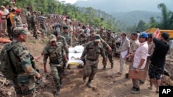 Army soldiers and rescue workers recover bodies of landslide victims even as they try to pull out two buses that were covered in mud after a landslide in Urla village, Himachal Pradesh state, India, Aug. 13, 2017.