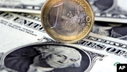 FILE - A euro coin sits atop US one-dollar notes in Gelsenkirchen, Germany.
