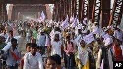 Những người hành hương theo đạo Hindu mang theo cờ tôn giáo đi trên một cây cầu đông đúc sau khi một vụ giẫm đạp trên cầu xảy ra ở ngoại ô Thành phố Varanasi, Ấn Độ, ngày 15 tháng 10 năm 2016.