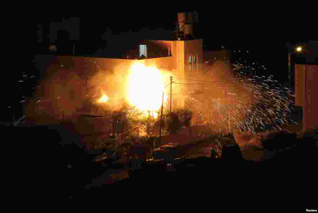 Flames are seen after a blast on the top floor of the family home of an alleged abductor in the West Bank City of Hebron. The bodies of three missing Israeli teenagers were found in the occupied West Bank and Israel vowed to punish Hamas, the Palestinian group it accuses of kidnapping and killing them.