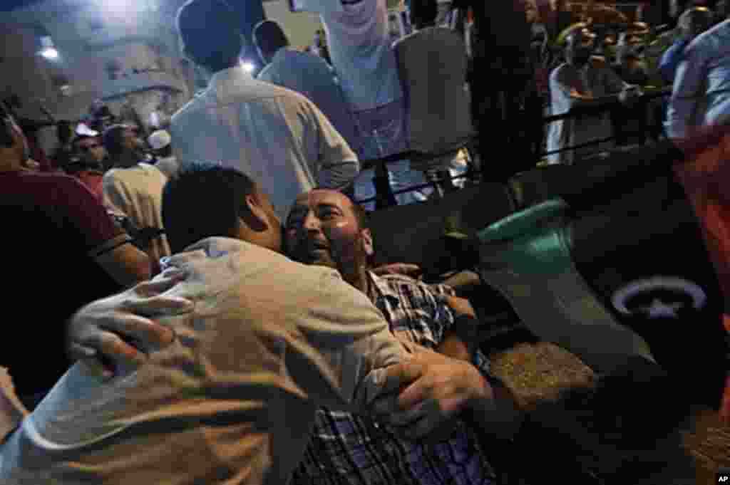 Libyans embrace each other as tens of thousands of Libyans celebrate the arrest of Qaddafi's son Saif al-islam and the fall of Tripoli to the Libyan rebels on Aug. 21, 2011 in Benghazi, Libya. (AFP)