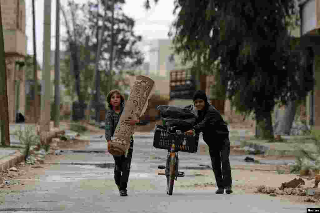 A boy pushes a bicycle as another one carries a carpet along a deserted street in Aleppo's al-Sakhour district, Syria.