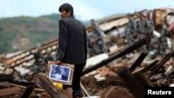 一名災民在廢墟中找到家庭照
