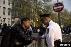 FILE - Ninth-grader Tremaine Holmes shakes hands with Captain Erik Pecha in front of the Baltimore Police Department Western District station in Baltimore, April 23, 2015.