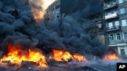 1月25日早上,和警察对峙的一名抗议者在乌克兰首都基辅市中心向火堆扔去一只轮胎
