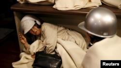 一名女士在日本南部地震后,躲藏在避难所里(2016年4月16日)