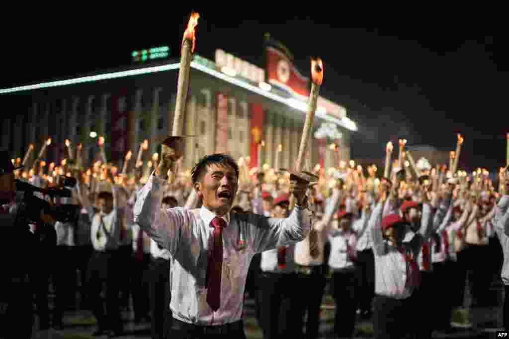 អ្នកស្ម័គ្រចិត្តចូលរួមនៅក្នុងការសម្តែងកាន់ភ្លើងនៅទីលាន Kim Il-Sung ក្នុងក្រុងព្យុងយ៉ាង កាលពីថ្ងៃទី១០ ខែតុលា ឆ្នាំ២០១៥ ដើម្បីប្រារព្ធខួបទី៧០នៃការបង្កើតគណបក្សកាន់អំណាចដែលមានឈ្មោះថា Workers' Party។