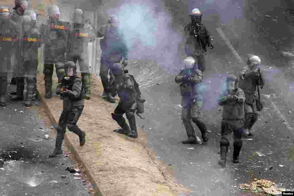 National Guards fire against demonstrators during a protest against Venezuelan President Nicolas Maduro's government in San Cristobal, about 410 miles (660 km) southwest of Caracas, February 27, 2014. Unrest sparked by student-led protests against Maduro'