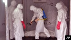 Health workers wearing protective gear spray the shrouded body of a man with disinfectant as they suspect he died from the Ebola virus, at a USAID, American aid Ebola treatment center at Tubmanburg on the outskirts of Monrovia, Liberia, Nov. 28, 2014.