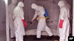 Zdravstveni radnici u zaštitnoj opremi prskaju telo osobe za koju se veruje da je umrla od ebole u okolini liberijske prestonice Monrovije