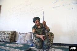 Heza, pejuang Yazidi dari Unit Perempuan Shengal (YPS), mempersiapkan senapannya di rumah yang ditinggalkan yang digunakan sebagai markas YPS di Al-Meshleb, pinggiran timur Raqa, 18 Juli 2017. (BULENT KILIC / AFP)