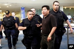 FILE - Dr. Yang Jianli, second from right, president of Initiatives for China, is escorted by United Nations security after staging a demonstration inside the lobby of the United Nations headquarters, Tuesday, Aug. 31, 2010.