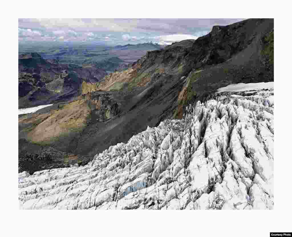Aliran gletser dari lapisan es Mýrdalsökull. Pegunungan bersalju di latar belakang adalah sisa gunung berapi besar yang meletus 53.000 tahun yang lalu. (Feo Pitcairn Fine Art)