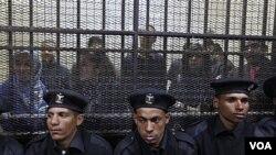 Polisi Mesir melakukan pengawalan atas puluhan aktivis HAM (belakang) dalam pengadilan pertama mereka di Kairo (26/2).
